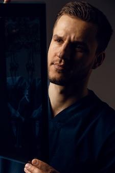 コロナウイルスcovid-19患者のx線スキャン。コンピュータ断層撮影。スキャンの写真を見ている医療ローブの外科医。健康診断のためのmri