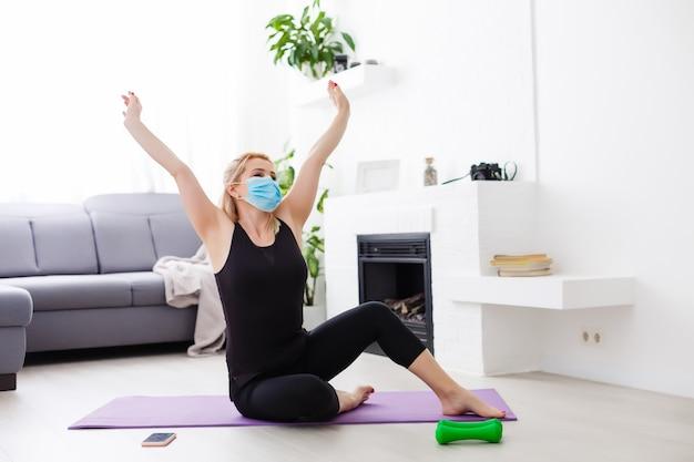 コロナウイルス。 covid-19(新型コロナウイルス感染症。マスク保護と検疫中に自宅でスポーツをしている若い美しい女性。外出禁止令。パンデミックによる感染を防ぎます。家で健康。