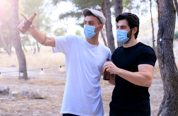 Группа молодого тысячелетнего мужчины, весело проводящего время в парке, пьющего на вечеринке с маской для лица, coronavirus, covid-19 - друзья собираются после блокады в аперитиве