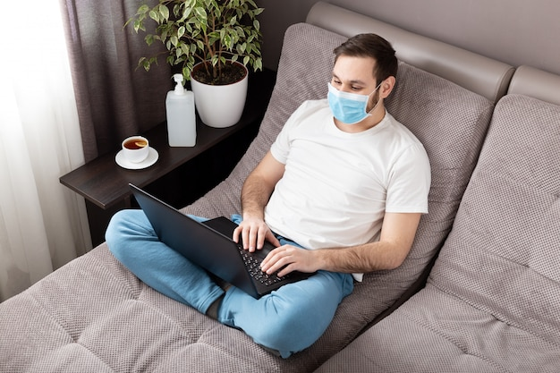 Домашнее рабочее место. укомплектуйте личным составом фрилансера в лицевой хирургической маске работая от дома используя компьтер-книжку. уютный домашний офис на диване. coronavirus covid-19 социальный дистанционный карантин