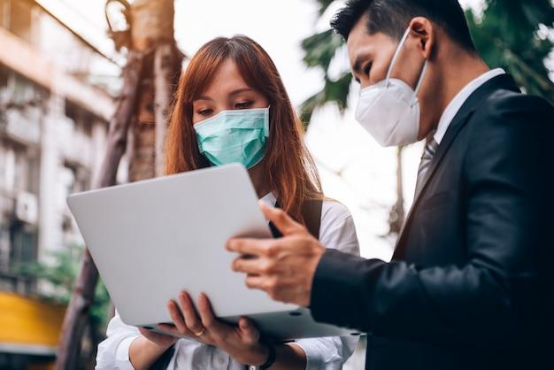 新しいビジネスのために屋外の場所で働いて調査しているアジアのビジネス人々、彼らはインフルエンザとcoronavirus covid-19を防ぐために保護マスクを着用しています