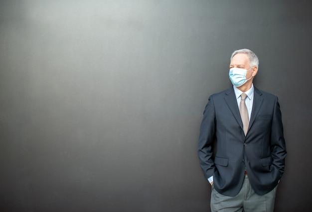 コロナウイルスcovidコンセプト、黒い壁の横に立っているマスクされたシニアビジネスマン