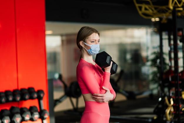 Профилактика коронавируса covid, фитнес-девушка с медицинской маской, держащая гантель. борьба с вирусами.