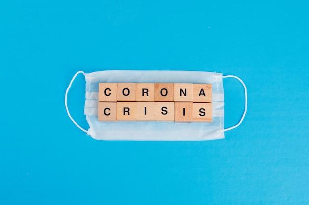 Concetto di crisi del coronavirus con la maschera medica, cubi di legno sulla disposizione blu del piano della tavola.