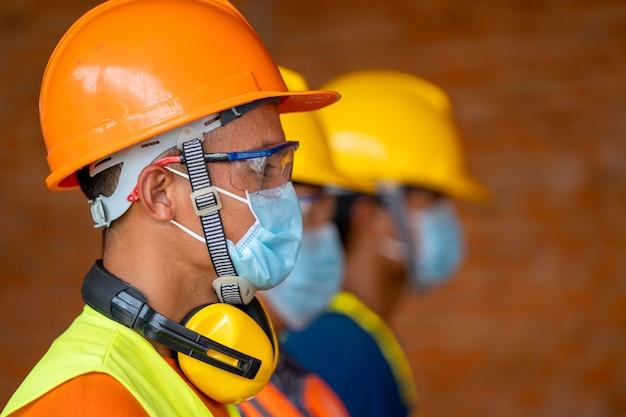 Техник надевает защитные маски безопасности для coronavirus disease 2019 (covid-19) на машиностроительном заводе, coronavirus превратился в глобальную чрезвычайную ситуацию.