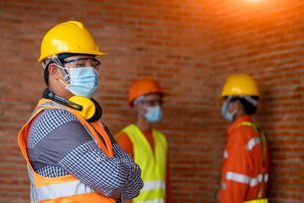 Группа профессиональных инженеров надевает защитные маски безопасности для coronavirus disease 2019 (covid-19) на машиностроительном заводе, coronavirus превратился в глобальную чрезвычайную ситуацию.