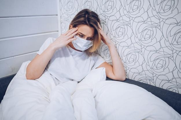 Симптомами коронавирусной болезни (covid-19) являются насморк, боль в горле, кашель и лихорадка. молодая женщина, больная коронавирусной вирусной инфекцией, распространяющей вирус короны. пациент лежал в постели дома на карантине