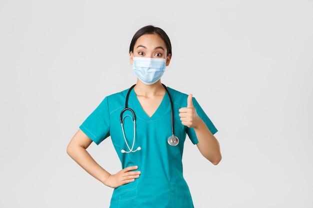, 코로나 바이러스 질병, 의료 종사자 개념. 즐겁고 감동적인 아시아 여성 의사, 스크럽 및 의료 마스크의 간호사, 승인에 엄지 손가락 표시, 동의 또는 칭찬 작업.