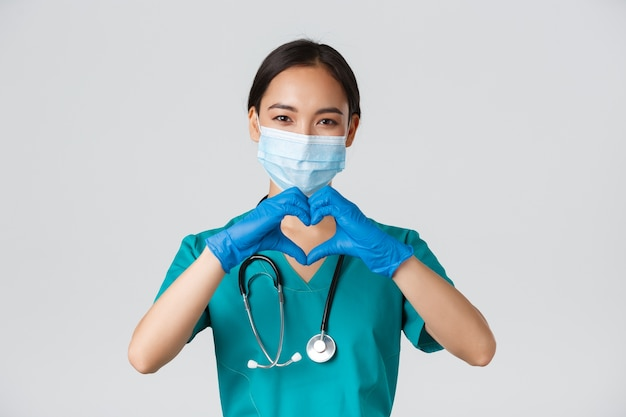 、コロナウイルス病、医療従事者の概念。魅力的な笑顔のアジア女性医師、医療用マスクとゴム手袋の医師のクローズアップは、患者のケアを提供し、心のジェスチャーを示す