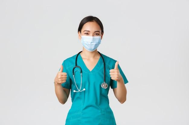 , коронавирусная болезнь, концепция работников здравоохранения. уверенный, улыбающийся азиатский врач, медсестра в скрабах и медицинской маске обеспечивают хорошее качество обслуживания, показывают одобрительные пальцы