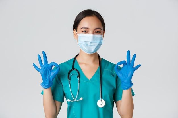 , коронавирусная болезнь, концепция работников здравоохранения. уверенно улыбающаяся азиатская женщина-врач, медсестра в медицинской маске и перчатках, демонстрирует одобрительный жест, белая стена