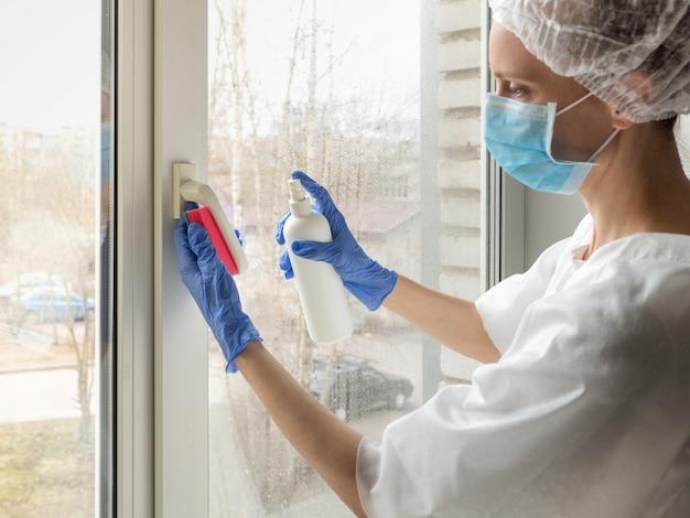 Коронавирусная дезинфекция. люди делают дезинфекцию на окнах. доктор в резиновых перчатках дезинфицирует оконную ручку дезинфицирующим средством и губками