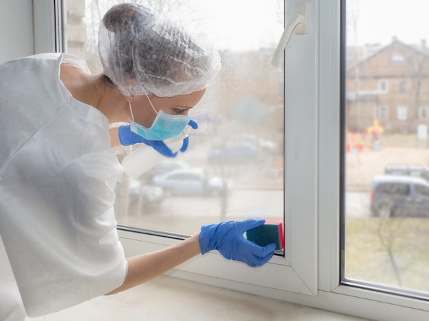 Coronavirus disinfection. people in making disinfection on windows. doctor in rubber gloves disinfects windows with disinfectant and sponges