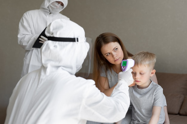 코로나 바이러스 의사는 소년 체온을 확인합니다.