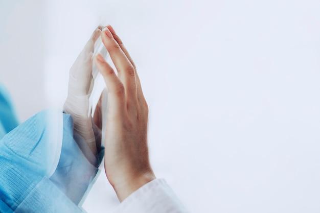 ガラス窓から家族の手に触れるコロナウイルス医師