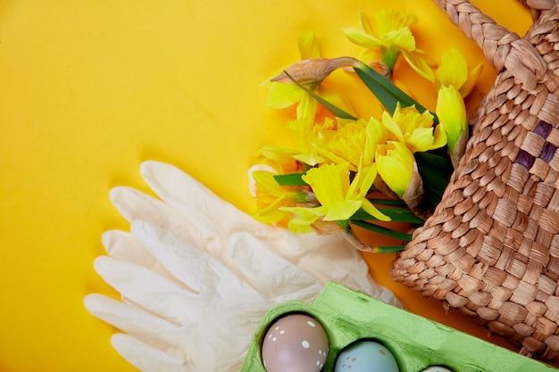 コロナウイルスイースターシンボルの卵と保護用医療用手袋、コロナウイルスの流行、検疫のためのイースター休暇のための概念の近くのバスケットに水仙の花。フラットレイ