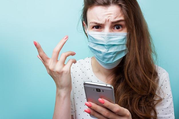 Коронавирусная эпидемия. девушка в одноразовой медицинской маске и больничной одежде держит смартфон в руке. возмущенный, злой, нервный из-за шокирующих новостей