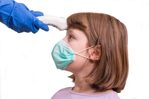 코로나 바이러스 확산 개념 : 소아과 의사 또는 의사가 바이러스 증상에 대한 적외선 이마 온도계 (온도계 총)를 사용하여 초등학생 소녀의 체온을 확인합니다-