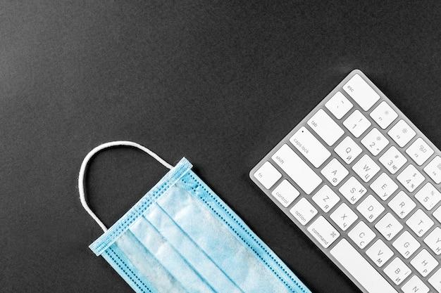 Коронавирус, маска для лица и белая клавиатура, изолированные на черном фоне. работать удаленно или работать из дома концепции.