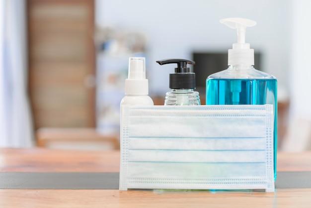 コロナウイルス細菌保護マスクとジェルアルコールまたは手消毒スプレーボトルを手で洗ってコロナウイルスを保護する木製のテーブルに設定