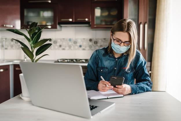 コロナウイルス。電話でソーシャルアプリをチェックするマスクの女の子。女性は仕事、学び、ラップトップコンピューターを使用しています。検疫。家にいる。フリーランサー。書く、タイプする。コミュニケーションとテクノロジーのコンセプト。