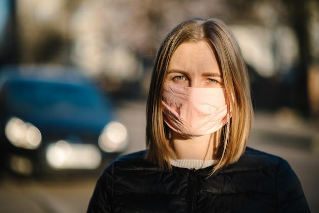 コロナウイルス。通りでcovid-19パンデミック中にマスクを持つ少女