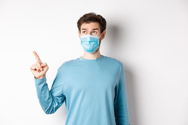 コロナウイルス、健康と検疫の概念。白いスタジオの背景の上に立って、左上隅のバナーを指して見て、医療マスクの好奇心旺盛な男。