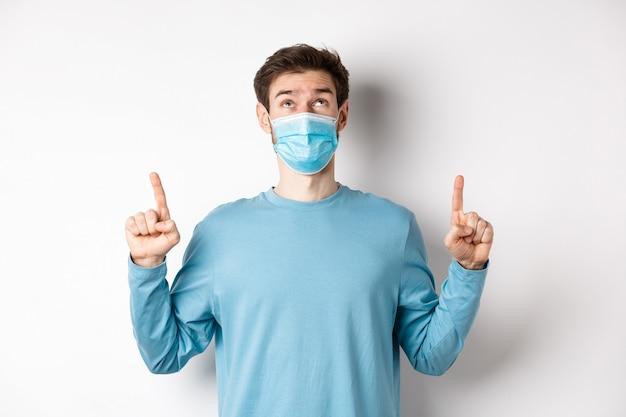コロナウイルス、健康と検疫の概念。好奇心旺盛な男は、白い背景の上に医療マスクに立って、上にバナーを読んで、指を上に向けて見ています。