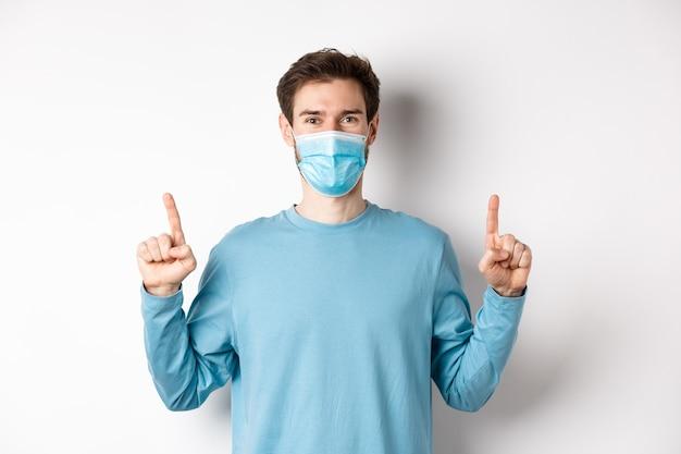 コロナウイルス、健康と検疫の概念。上にバナーを表示し、指を上に向けて医療マスク、白い背景を身に着けているハンサムな白人男性モデル。