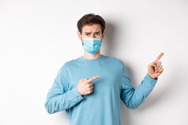 コロナウイルス、健康と検疫の概念。医療マスクの眉をひそめている悲しい男、疑わしい顔で指を右に向け、白い背景の上に立っています。