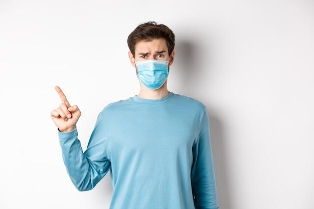 코로나 바이러스, 건강 및 검역 개념. 의료 마스크 가리키는 손가락에 회의적인 남자 로고에 왼쪽, 실망, 흰색 배경 위에 서있는 인상을 찌푸리고.