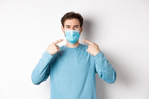 コロナウイルス、健康と検疫の概念。パンデミック、白い背景の間に予防措置を使用するように求めて、彼の医療マスクを指しているカジュアルな服を着た若い白人男性。