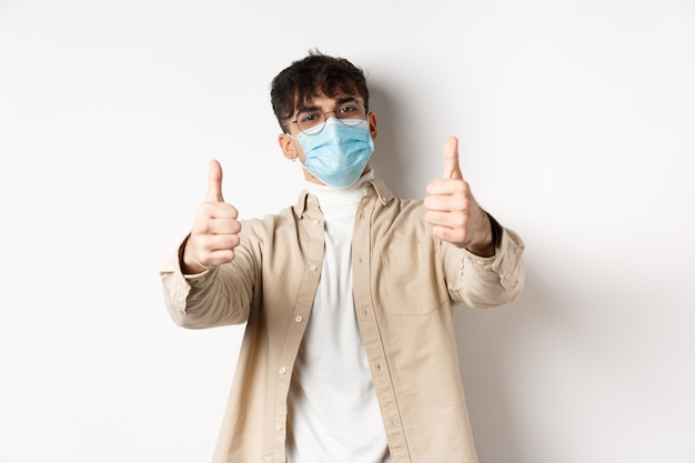 Coronavirus, health and real people concept. smiling guy in medical mask showing thumbs up, wearing glasses, standing on white wall.