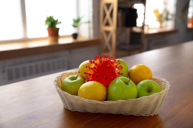 いつものことに隠れているコロナウイルス-果物や食べ物の浄化と鮮度をチェックしてください。束の1つ。台所のテーブルにリンゴ、オレンジ、レモン。パンデミック、エピデミックの概念、消毒。