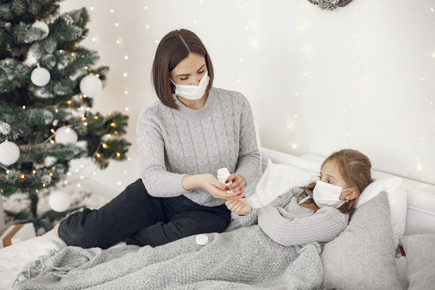 어린이의 코로나 바이러스. 딸과 어머니. 침대에 누워있는 아이. 의료 마스크에 여자입니다.