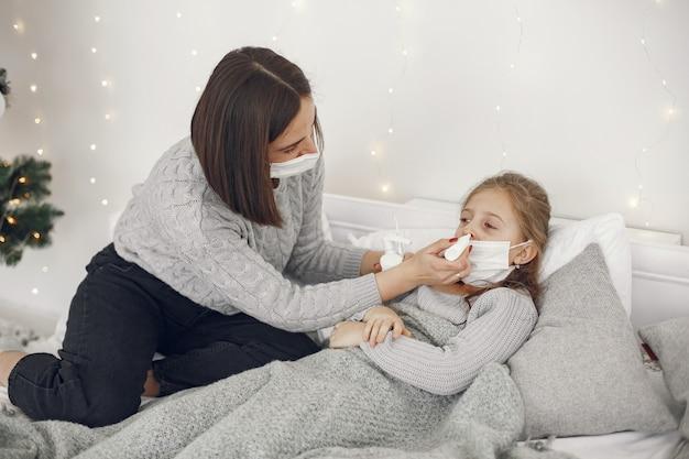 Коронавирус у ребенка. мать с дочерью. ребенок, лежащий в кровати. женщина в медицинской маске.