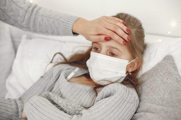 子供のコロナウイルス。娘と母。ベッドに横たわっている子供。医療用マスクの女性。