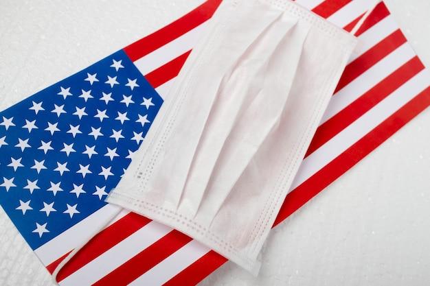 アメリカのコロナウイルス。アメリカの旗を背景にした医療用抗菌マスク