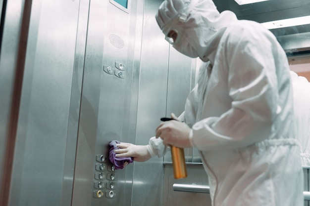 Coronavirus infection. paramedic in protective mask and costume disinfecting an elevator with sprayer,