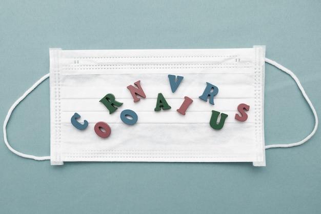 青い背景の医療用白いマスクの文字からのコロナウイルスの碑文