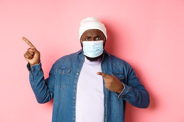Coronavirus, stile di vita e concetto di pandemia globale. uomo afroamericano arrabbiato e deluso in maschera facciale che punta a sinistra, fissando la telecamera dispiaciuta, sfondo rosa.
