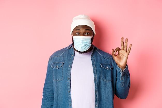 Coronavirus, stile di vita e concetto di distanza sociale. impressionato uomo afroamericano in maschera facciale, mostrando segno ok, mi piace e d'accordo, in piedi su sfondo rosa