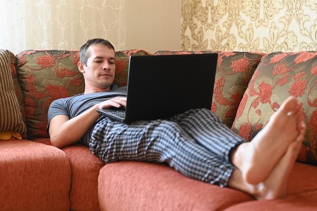 コロナウイルス。保護マスクを身に着けているコロナウイルスの検疫中の男、彼はソファに横になっています。
