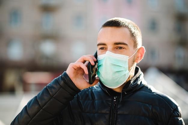 コロナウイルス。通りを歩いて医療用防護マスクを着用し、携帯電話で話している人。 covid-19、インフルエンザを防ぎます。ウイルス、パンデミック、パニックの概念。