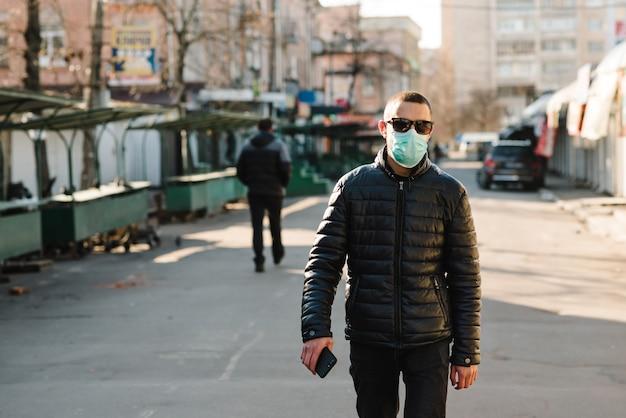 コロナウイルス。通りを歩いて医療用防護マスクを着た男。コロナウイルスcovid-19。大気汚染、ウイルス、中国のパンデミックのコンセプト。ウイルス、パンデミック、パニックの概念。