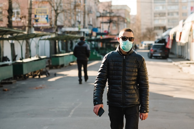 Coronavirus. man wearing medical protective mask walking on street.  corona virus covid-19. air pollution, virus, chinese pandemic concept. virus, pandemic, panic concept.