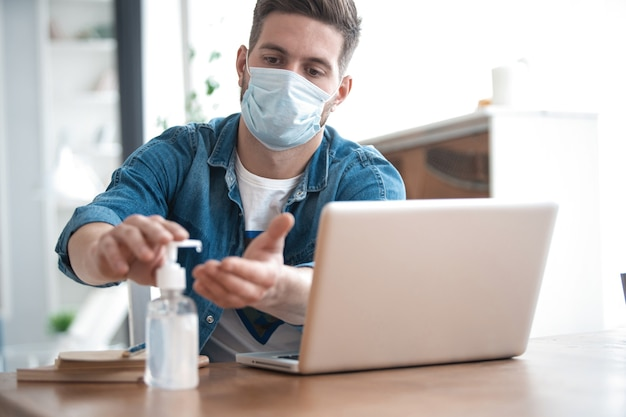 Coronavirus. man working from home wearing protective mask. cleaning his hands with sanitizer gel.