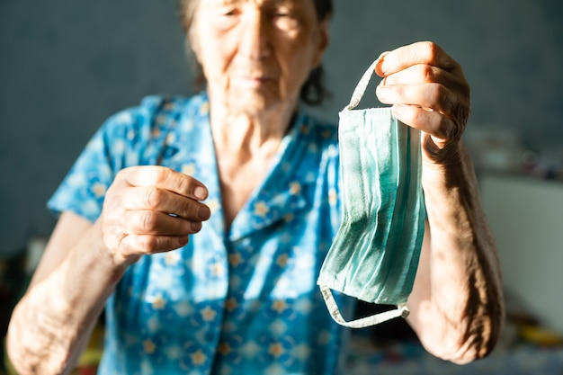 코로나바이러스, 마스크를 쓴 여성, 코로나바이러스에 대한 보호 마스크를 들고 있는 86세. 안면 마스크를 쓴 노부인