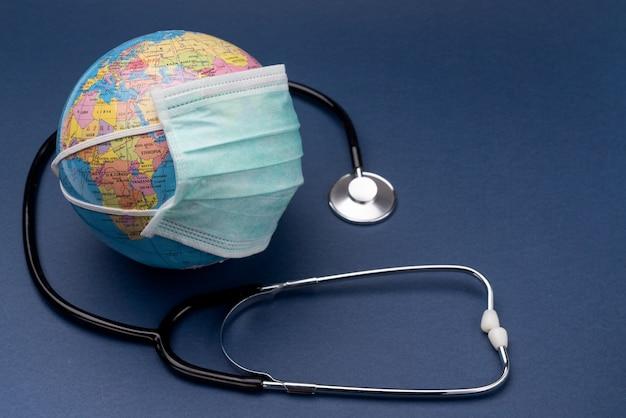 A coronavirus medical mask with a stethoscope is put on the globe. european union. europe.