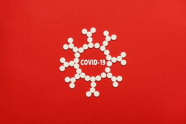 コロナウイルス顕微鏡構造の概念。コピーの空の空白スペースで赤い背景の上に分離された小さな白い丸い丸薬で作られたコロナウイルスの上部オーバーヘッドフラットレイ写真